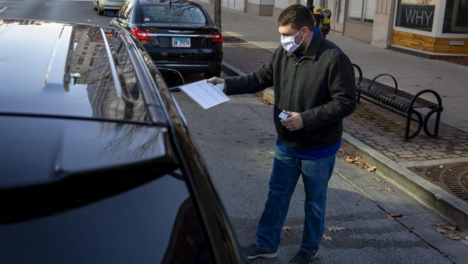 Neil Calderon, the treasurer for the Sangamon County Democratic Party, hands out a clipboard to collect signatures for candidates during a drive-thru petition signing at the Sangamon County Democratic Party Headquarters on East Monroe Street, Saturday, Dec. 5, 2020, in Springfield. The drive-thru system was a safe way to stay socially distant during the COVID-19 pandemic while collecting signatures for candidates for the upcoming consolidated election.