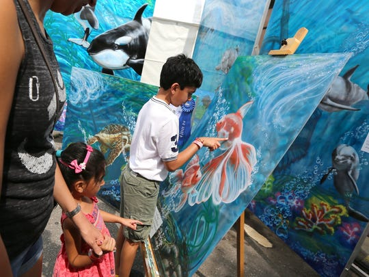 Aarya Mohey, 9, of Franklin and his sister Aanya Mohey, 4, examine the best-in-show winner at the 2014 Arts, Beats & Eats in Royal Oak. The goldfish paintings were created by artist Jennie M. Burt of Monroe.