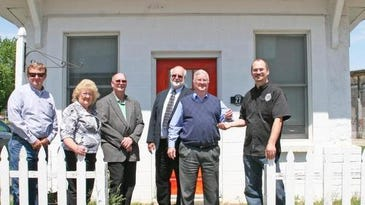 Andy Hansen hands the keys to the new Carlisle Chamber of Comerce building off to Carlisle Chanber President Todd Hugen. The building, located at 27 School Street. Pictured are Scott James, of Carlisle; Carlisle Chamber Exeuctive Director Barb Rasko; brothers Andy Hansen, Jim Hansen, Perry Hansen and Carlisle Chamber President Todd Hugen.