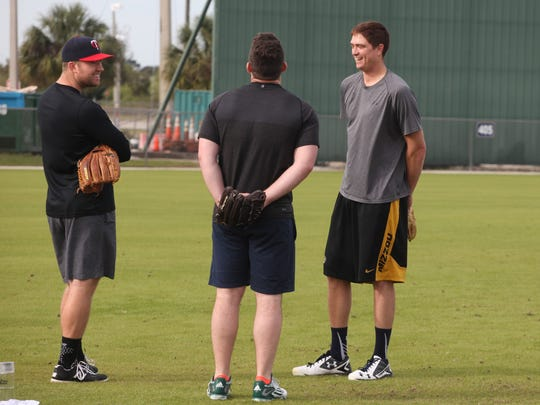 Alex Wimmers, left, Liam Hendriks, and Kyle Gibson hang out on the practice fields at the CenturyLink Sports Complex on Thursday morning.