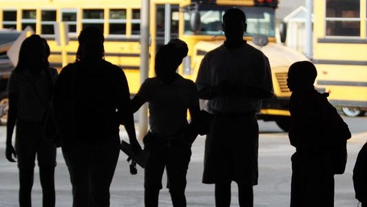 Students at Acadian Middle get off of buses and onto campus. One major goal of a new rezoning process is to reduce transportation costs.