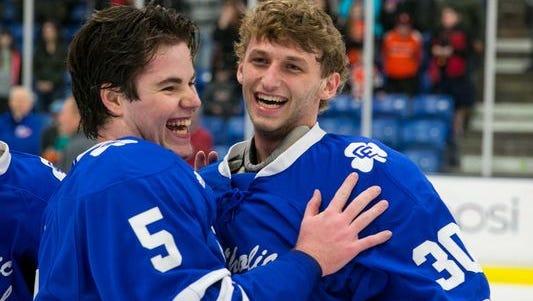 Mitchel Kiefer, right, played goalie on his high school hockey team.