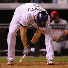 DENVER, CO - AUGUST 15:  DJ LeMahieu #9 of the Colorado Rockies strikes the ground as he reacts to striking out against Johnny Cueto #47 of the Cincinnati Reds with the bases loaded to end the sixth inning at Coors Field on August 15, 2014 in Denver, Colorado.  (Photo by Doug Pensinger/Getty Images)