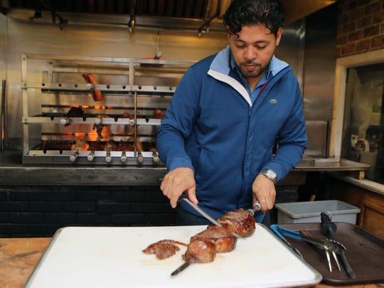 Josh Souza slices churrasco meat at USA Brazilian on Gramatan Avenue in Mount Vernon.