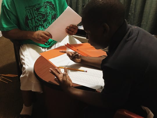 Quinton Dailey helps Drayon, 10, with homework. The