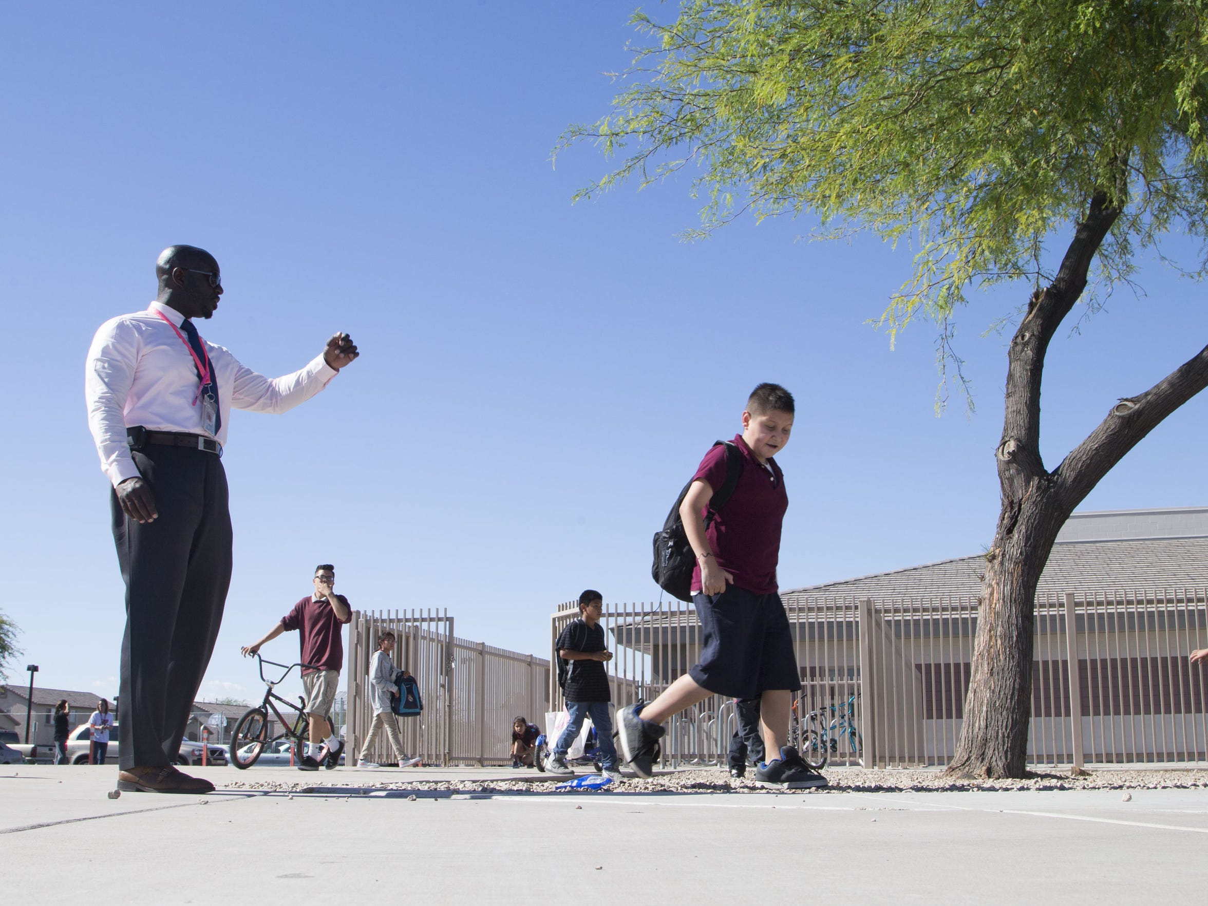 Principal Eric Atuahene keeps an eye on his students as they go home after a school day.