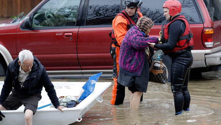 Rescue crews take out residents from a flooded neighborhood