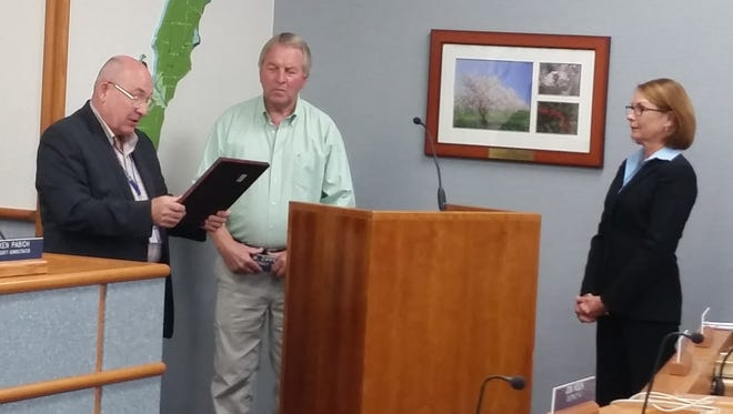 Door County Board Chairman David Lienau, left, reads from a commendation issued by Gov. Scott Walker recognizing retiring county supervisor Leo Zipperer's decades of service to county government. Looking on is the person who was elected last month as Zipperer's successor, Supervisor Linda Wait.