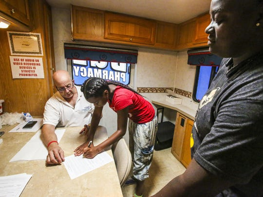 Amani Miller, 13 of Lehigh Acres, fills out paper work