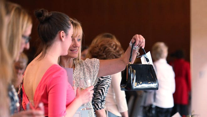 Women admire the purses at the 2013 A Purse for Change auction.
