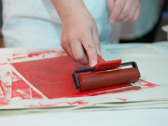 A roller is used to during the printmaking process