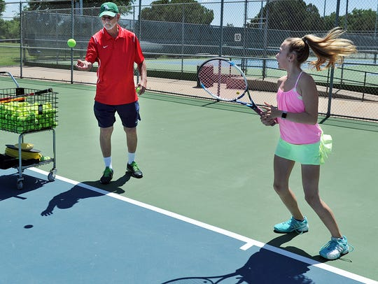 In this file photo, Johnny Simmons, tennis pro, works with Jaci Nichols on fundamentals. Simmons will no longer be the manager of the city's tennis centers, but remain a tennis coach/instructor. A contract with Lifetime Tennis Incorporated will be considered Tuesday for management services of Hamilton and Weeks Tennis Centers.