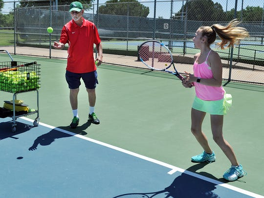 Johnny Simmons, tennis pro for the Hamilton Park Tennis Center, works with Jaci Nichols on fundamentals. Simmons is marking his 47th year working as a pro here. Following a contract change if approved by city council Tuesday, Simmons will be the head tennis pro at a single city tennis center, based at Hamilton.