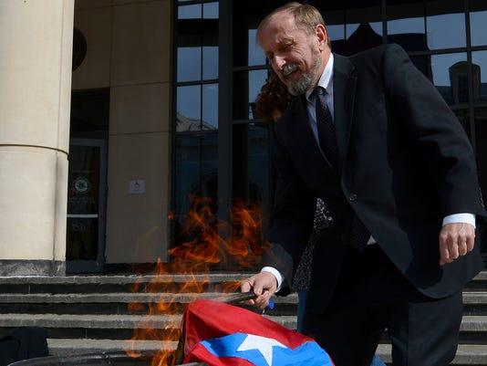 Activist burns flag outside Judicial Center