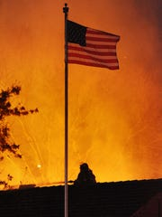 A firefighter, bottom, sprays water atop the historic