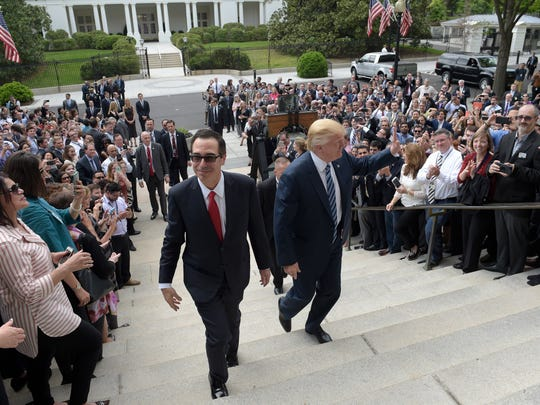 President Donald Trump (right) and Treasury Secretary Steven Mnuchin arrive at the Treasury Department in Washington on April 21, 2017, where the president was to sign an executive order to review tax regulations, as well as two memos to potentially reconsider major elements of the 2010 Dodd-Frank financial reforms passed in the wake of the Great Recession.