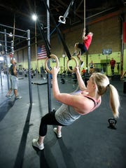 Lauren Hester does ring rows as she works out at CrossFit Riverfront Thursday. She gave birth to a daughter in April.