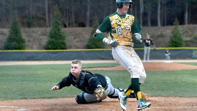 Reynolds' Josh Dotson score a run just ahead of Tuscola catcher Patrick Broom during their game at Reynolds High School on Friday, March 23, 2018. The Rockets defeated the Mountaineers 10-0 in five innings.