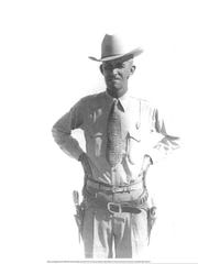 Outdoor standing portrait of Sheriff Dwight Lee (50) in hat, with holstered pistols, hands on hips. Circa 1949, September.   Bob Nymeyer Photo Collection