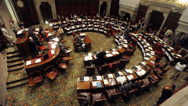 Members of the New York state Senate work in the Senate Chamber as the legislative session winds dow on June 20, 2012.   (AP Photo/Tim Roske)