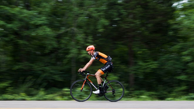 Knoxville cyclist Stephen Bassett rides his bike outside his South Knoxville home Thursday, June 14, 2018. Bassett will compete in the USA Cycling's Pro Road Championships in Knoxville June 21-24.