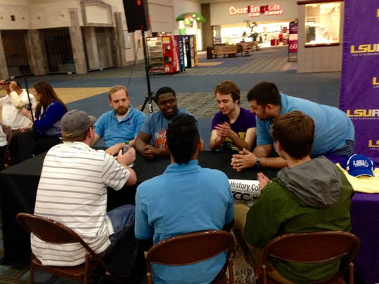 Students, faculty and staff of Louisiana State University of Alexandria discuss how they will answer a black history question in a quiz bowl competition against Central Louisiana Technical Community College at the Alexandria Mall on Thursday.