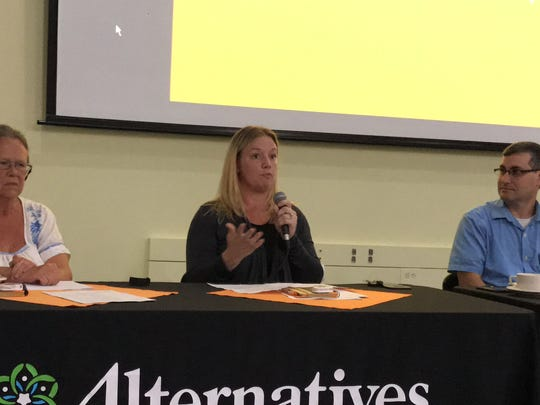 Megan Ward, a worker at Alternatives FCU, talks about being on a living wage. At left is  Deb Dietrich, the executive director of Opportunities, Alternatives and Resources (OAR), and at right is Eric Levine, acting CEO and general counsel at Alternatives FCU.