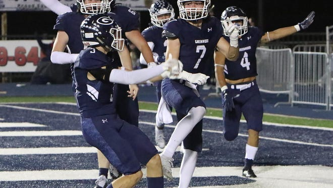 Greenwood's Colin Daggett (7) celebrates with the Bulldog defenders after scoring on a pick-six, Friday, Nov. 13, in the second quarter against West Memphis at Smith Robinson Stadium.