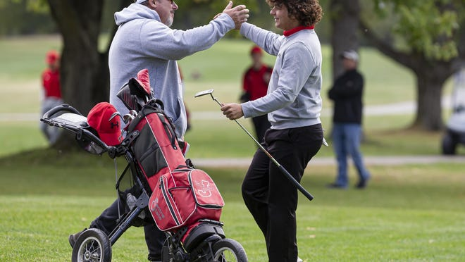 Jacksonville High School senior Aydin Folker gets a hug from his father, Aaron Folker, after walking off the 18th green with a 2-under-par 70 to win the Central State Eight Conference Boys Golf Tournament at Lincoln Greens Golf Course, Thursday.