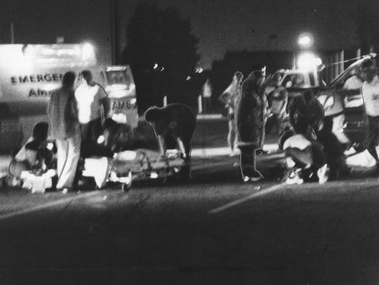 Emergency personnel attend to a victim of the Speedway