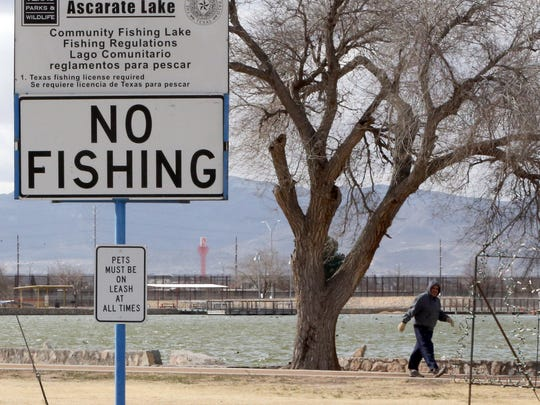 A man walks Tuesday along the path around Ascarate Lake. A sign near the lake warns against fishing. Some dead carp, shad and catfish were seen floating in some areas of the lake, while some live fish were seen swimming near the lake's edge.