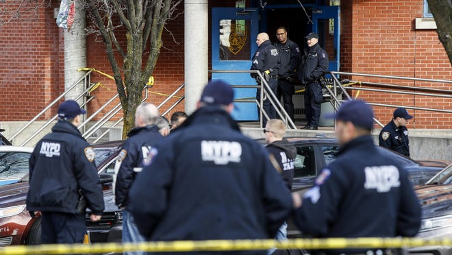 New York police stage outside the 41st Precinct at the scene of a police-involved shooting in New York.