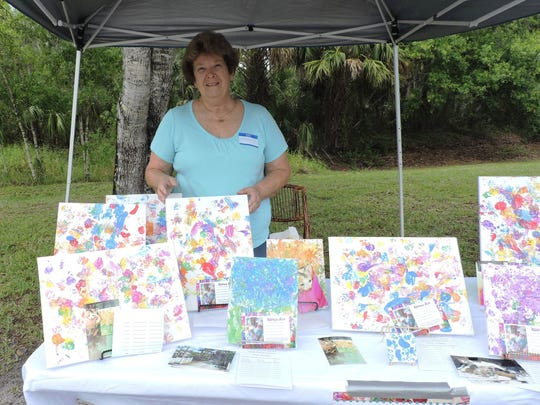 Sharyon Daigneau exhibits art painted by the kittens at the Caring Fields Felines' kitten shower.