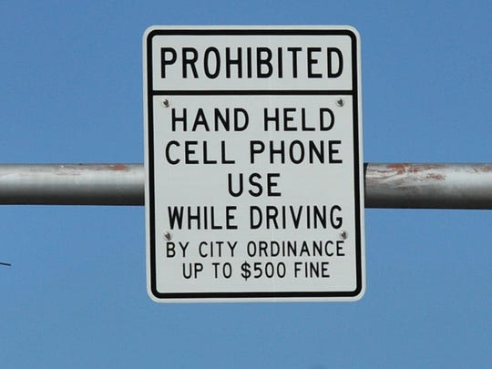 A sign warns drivers of the new city law prohibiting drivers from using handheld cellphones or devices while driving.