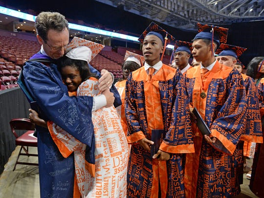 Carolina High and Academy principal Michael Delaney hugs a graduate during the school's commencement exercises on Wednesday, June 1, 2016 at Bon Secours Wellness Arena.