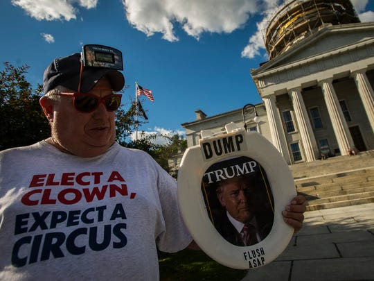 Brian Stoops of Waterbury shows off his home-made protest sign, made from a toilet seat he bought at Walmart, on the steps of the Statehouse in Montpelier, Vt., on Monday, June 25, 2018. Hundreds gathered to protest President Trump's immigration policies, specifically the practice of separating immigrant children from their parents at the border.