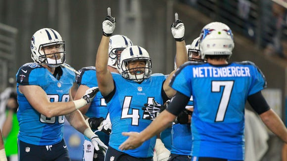 Tennessee Titans running back Jackie Battle (44) celebrates with quarterback Zach Mettenberger, right, and tight end Chase Coffman, left, after scoring a touchdown against the Green Bay Packers in the fourth quarter on Saturday.