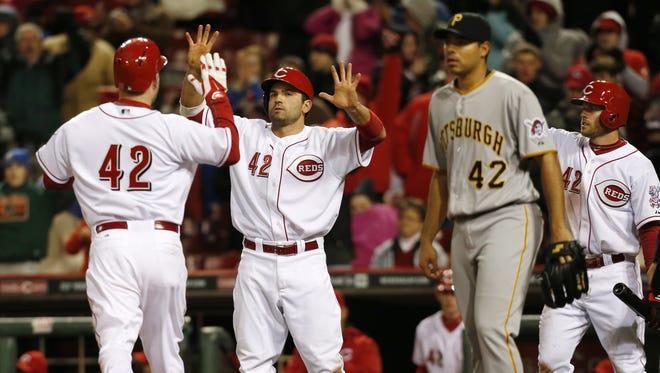 Cincinnati Reds third baseman Todd Frazier (21) and first baseman Joey Votto (19) scored on a seventh inning base hit by catcher Devin Mesoraco (39).