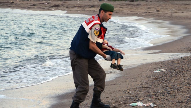 A Turkish police officer carries the body of Aylan Kurdi, 3, on Sept. 2, 2015, on a beach near Bodrum, Turkey. The boy and other migrants drowned when  boats carrying them to the Greek island of Kos capsized.