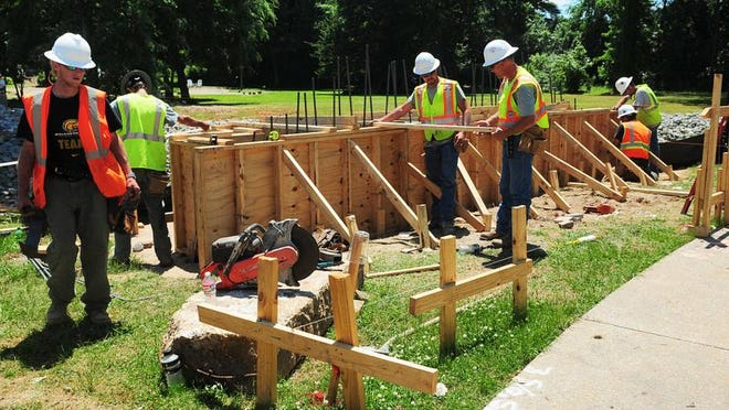 Holliday Construction, LLC employees work on the north abutment of the new bridge over Gordon's Creek at Town Square Park. The bridge will be completed during Phase I of the nine-phase Gordon's Creek Linear Park project.