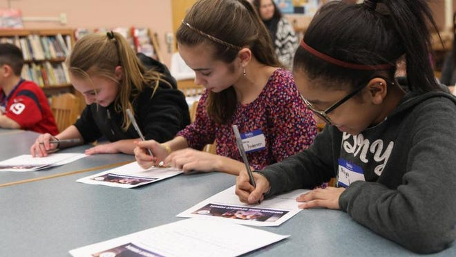 Nicole Guadagno, 12, Emma Anderson, 11 and Naiya Lacayo, 11, write observations about Common Core during a roundtable workshop at Copper Beech Middle School in Shrub Oak on Feb. 11. The event, sponsored by state Sen. Greg Ball, was attended by 70 students, parents and educators.