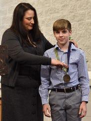 Amanda Kopp gives Caleb White receives the Virtue,