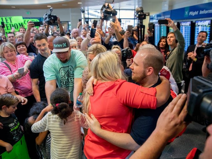 Josh Holt, right, is greeted by family and friends
