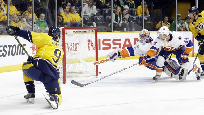 Predators center Filip Forsberg (9) shoots wide of the net as Islanders goalie Thomas Greiss (1) and Calvin De Haan (44) reach for the puck in the second period Thursday.
