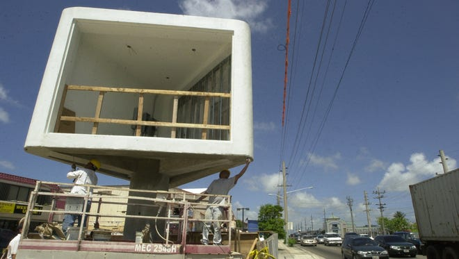 In this file photo, Santanio Bius, 31, left, and Al Gan, 39, in March 2004 work on the concrete structure that TriVision Media Group was developing into a three-faced digital display for advertisements on the Paul's Plaza side of the ITC intersection in Tamuning.