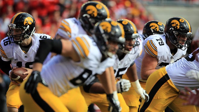 Iowa linemen push forward as quarterback C.J. Beathard drops back during the Hawkeeys' game against Wisconsin at Camp Randall in Madison on Saturday, Oct. 3, 2015.