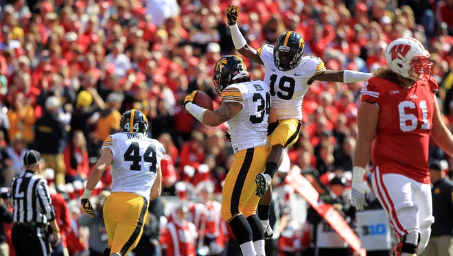 Iowa's Miles Taylor (19) and Nate Meier celebrate after Meier's fumble recovery off a Drew Ott sack during their 10-6 win at then-No. 19 Wisconsin.