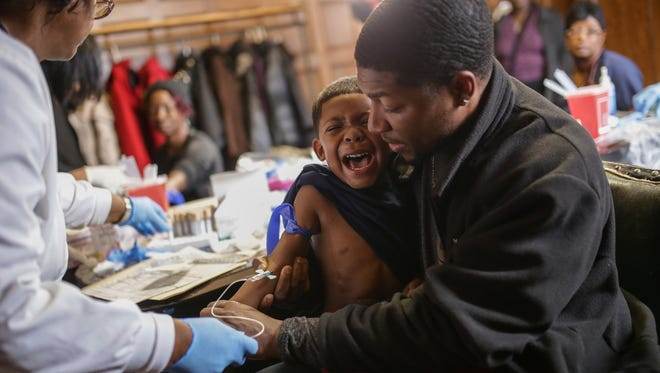 Mike Henry Sr. of Grand Blanc holds his grandson, Kaiden Olivares, 3, as he screams while giving a blood sample to be tested for lead on Saturday, Jan. 23, 2016, at the Masonic Temple in downtown Flint.
