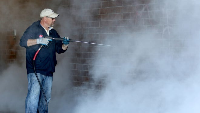 Doug Mack, a maintenance worker with the Salem-Keizer School District, uses a pressure washer to remove spray paint vandalism from the walls and sidewalks at McKay High School in Salem on Wednesday, April 6, 2016.