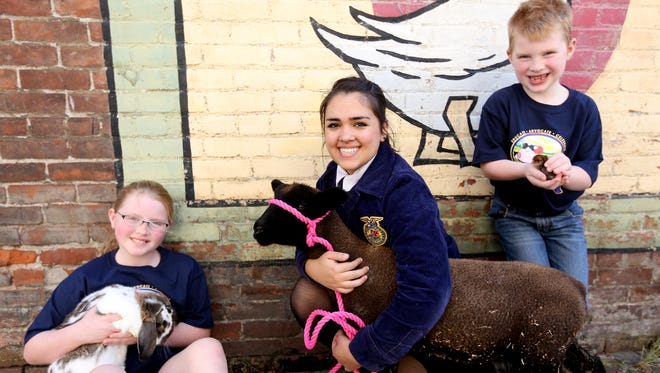 Oregon AgFest representatives Hanna Krahmer, 9, from left, holds a rabbit named Martin, Faith Wilson, 18, holds Sassy, a lamb, and Mason Krahmer, 6, holds a chick for a photo during the Statesman Journal's Holding Court at the Court Street Dairy Lunch in downtown Salem on Tuesday, April 19, 2016.